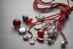 Red stringed necklace with beads and trinkets Stock Image