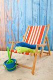 Red striped beach chair. And toys in sand Stock Photography