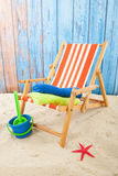 Red striped beach chair. And toys in sand Stock Photos