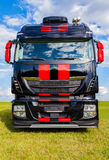 Red striped big rig on grass. And blue sky royalty free stock photography