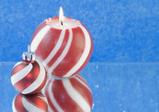 Red striped Christmas candle blue background Stock Photo