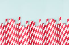 Red striped cocktail straws on pastel mint color as abstract joyful background, border with copy space. Red striped cocktail straws on pastel mint color as royalty free stock photos