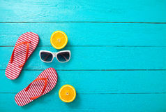 Red striped flip flops, red sunglasses and orange fruit on blue wooden background. Top view and summer time. Royalty Free Stock Image
