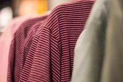 Red striped t-shirts on the hanger in mall stock images