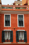Red stucco house with old green shutter windows in Monaco Stock Images
