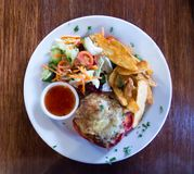 Red stuffed capsicum pepper with cheese, potato wedges, dipping sauce and fresh salad. Served on a white plate royalty free stock images