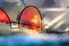 Sunglasses with reflection of summer beach with black sand, sun and sea. Capri Italy. Red stylish woman Sunglasses with reflection of summer beach with black royalty free stock image