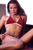 Red suede bikini portraits. Young female fitness model poses in a red suede bikini royalty free stock photography