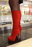 Red suede boots. Details of the red suede boots on the female legs Royalty Free Stock Photography