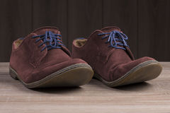 Red suede shoes with blue laces. Royalty Free Stock Image