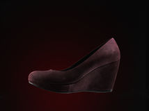 Red suede shoes. Over dark red background Stock Photo
