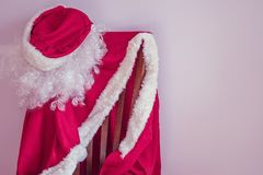 Approaching the New Year!. The red suit of Santa Claus is waiting on the chair of the beginning of the holiday. Soon the New Year, there are last preparations Stock Photo