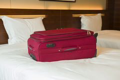Red suitcase on bed. Inside a hotel room Stock Image