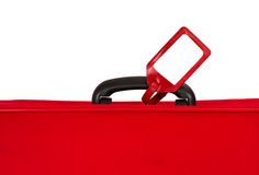 Red suitcase with blank tag over white. Closeup. Stock Image
