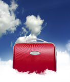 Red suitcase in clouds. Red suitcase siting in the middle of a cloud in a surreal fashion with sky background Stock Photo