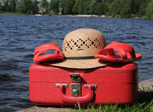 Red suitcase, straw hat, and sandals. Red suitcase, straw hat, and red sandals Royalty Free Stock Images
