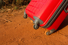 Red suitcase on wheels. Details. Unknown location, suitcase, left luggage, tourism, things, wait, road, roll, twist, sub-structure design, plastic, fashionable Stock Photography