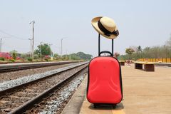 Red suitcase, woman hat with black ribbon on the railway. With sky at noon Royalty Free Stock Photo