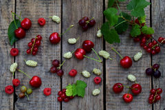 Red summer berries: cherry, mulberry, currant, raspberries on a wooden background Royalty Free Stock Image