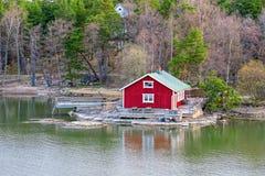 Red house on rocky shore of Ruissalo island, Finland. Red summer cabin or mokki on rocky shore of Baltic Sea. Ruissalo island, Turku archipelago, Finland Royalty Free Stock Image