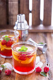 Red summer cocktail with lemons and raspberry Stock Photos