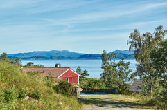 Red summer cottage among the rocks, fjord stock photography