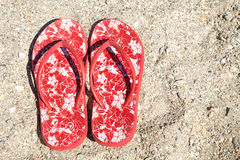 Red summer slippers on the beach Stock Photos
