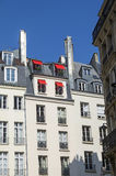 Red sun awnings. On the windows of the attic. Paris, France Royalty Free Stock Photos