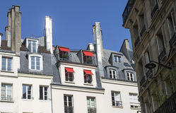 Red sun awnings. On the windows of the attic. Paris, France Stock Photos