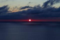 Red sun at dark blue sea Stock Photos