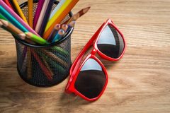 Red sun glasses with bunch of color pencils in a stand Royalty Free Stock Image