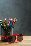 Red sun glasses with bunch of color pencils in a stand Stock Photography