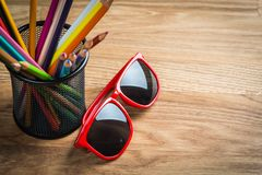 Red sun glasses with bunch of color pencils in a stand Royalty Free Stock Photography