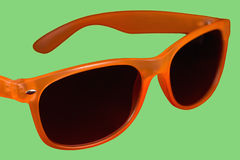 Red sun glasses. Isolated over the green background Stock Image