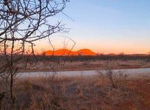 Red sun lit hills across African plain Stock Image