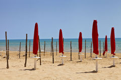 Red sun parasols on sandy beach summertime Stock Image