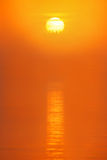 Red sun is rising in the morning mist. Over water surface from behind the forest Stock Image