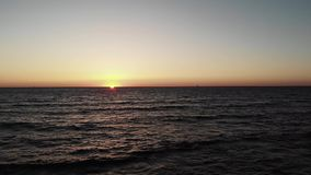 Red sun sets over ocean sea with waves with small black yacht boat in horizon. Sunset with sun path sun road towards the seashore. Red sun sets over ocean sea stock video footage