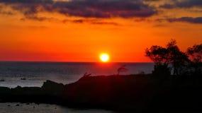 Sunset red sun behind mountain top stock photos