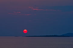 Red sun and sunset at sea below small cape at Sithonia Royalty Free Stock Photo