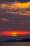 Red sun and sunset at sea below small cape at Sithonia Stock Photos