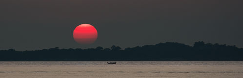 Red Sun at Sunset at Sea with Fishing Boat Stock Image