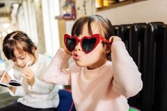 Cute funny dark-haired girl wearing bright red sunglasses stock photos