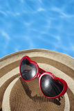 Red Sunglasses and Hat by a Blue Pool Royalty Free Stock Photography