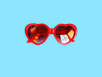 Red sunglasses with heart shape over colorful blue Stock Photography