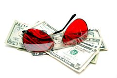 Red sunglasses resting on cash. Isolated on white Royalty Free Stock Images
