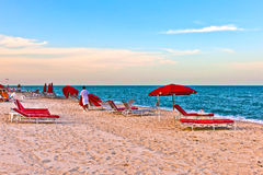 Red sunloungers and parasols at the beach. In sunset light Royalty Free Stock Images