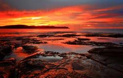 Red sunrise blankets Pearl Beach Australia Stock Images