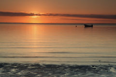 Red sunrise over calm sea. Glowing sunrise over Irish sea seascape with lonely boat and calm tranquil water surface Royalty Free Stock Images