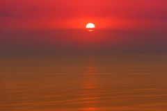 Red sunrise over the sea, horizontal shot. Beautiful sunrise over the sea in deep red colors with round sun and clouds Stock Photography